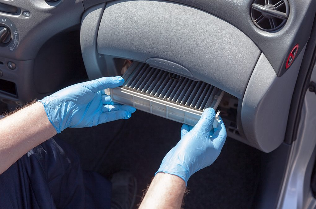 person removing air conditioner unit from car